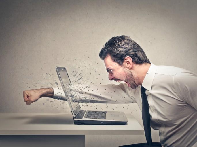 un homme se fâche contre son ordinateur